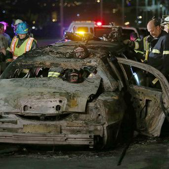 Firefighters investigate the scene of a limousine fire on a bridge in Foster City, California (AP/Oakland Tribune-Bay Area News Group)