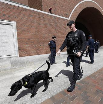 A Department of Homeland Security official walks with a bomb-sniffing dog at the federal court, in Boston (AP/Steven Senne)
