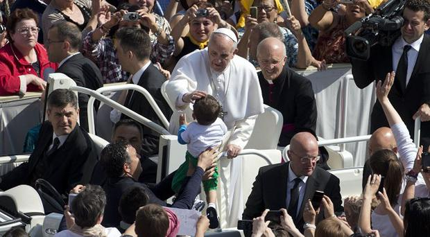 The pope is driven through the crowd in S. Peter's Square (AP)