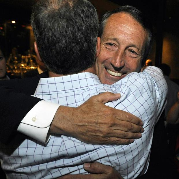 Former state Mark Sanford gets a congratulatory hug on winning his way back into politics (AP)