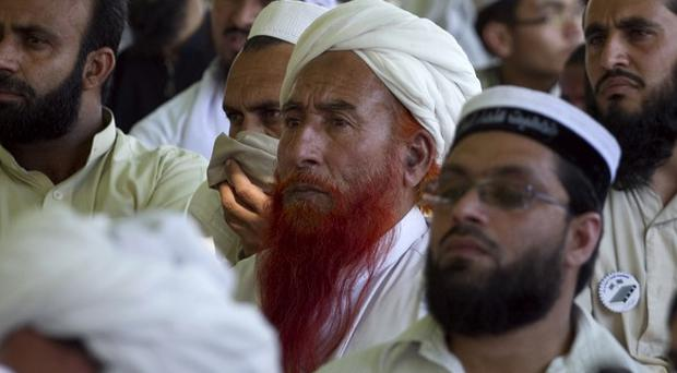 Supporters of a pro-Taliban religious group Jamiat-e-Ulema Islam (JUI-F), listen to their leader Maulana Shujaul Mulk, during an election campaign rally in Mardan, Pakistan (AP)