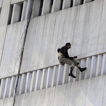 A man jumps from a nine-storey building that caught fire in Lahore (AP)