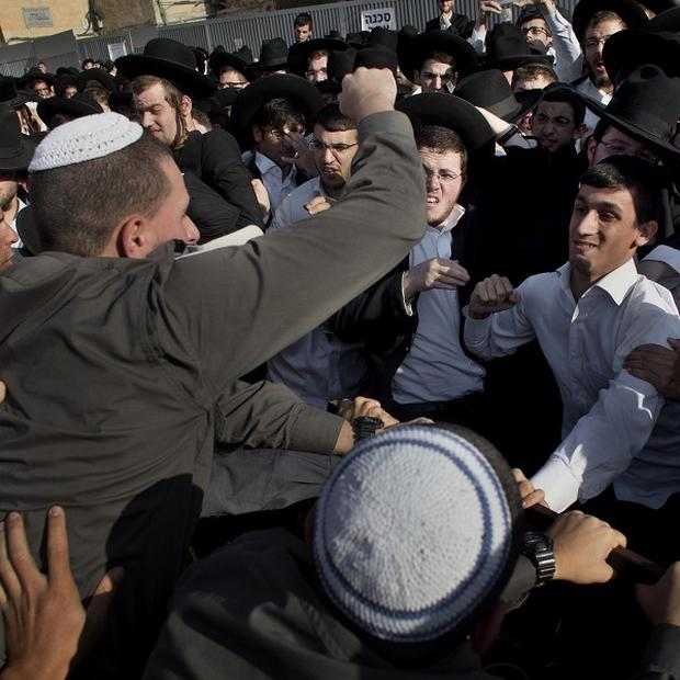 Ultra-orthodox Jewish men scuffle with Israeli security forcers during a prayer organized by the Women of the Wall organisation (AP)