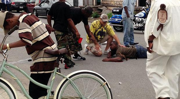 Bystanders comfort a shooting victim after gunmen injured at least a dozen people in New Orleans (AP/The Times-Picayune, Lauren McGaughy)
