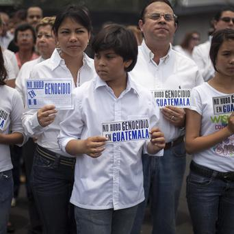 People hold a signs that read in Spanish 'there was no genocide in Guatemala' (AP/Luis Soto)