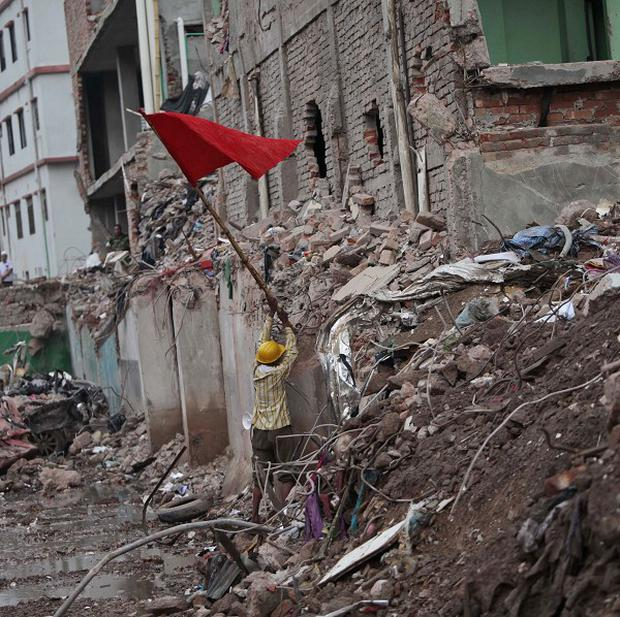 A Bangladeshi rescue worker puts a red flag, marking the end of rescue operations at the site where a garment-factory building collapsed (AP)
