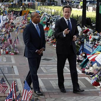 David Cameron and Massachusetts governor Deval Patrick visit the makeshift memorial to the Boston bomb victims in Copley Square (AP)