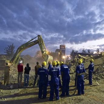 Rescue workers wait to search rubble after the completion of rescue work by heavy machinery at the scene of a building collapse in Rwanda (AP)