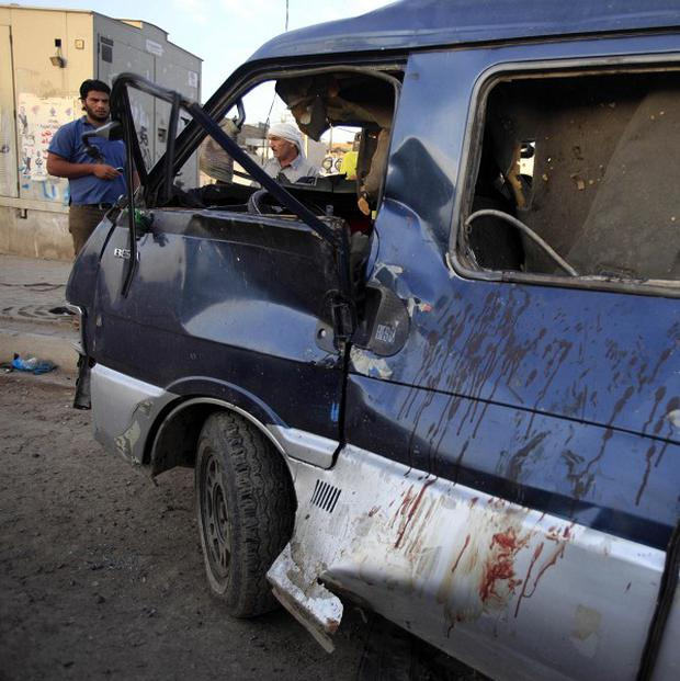 People inspect the aftermath of a car bomb attack in the Sadr City neighborhood in Baghdad, Iraq (AP)