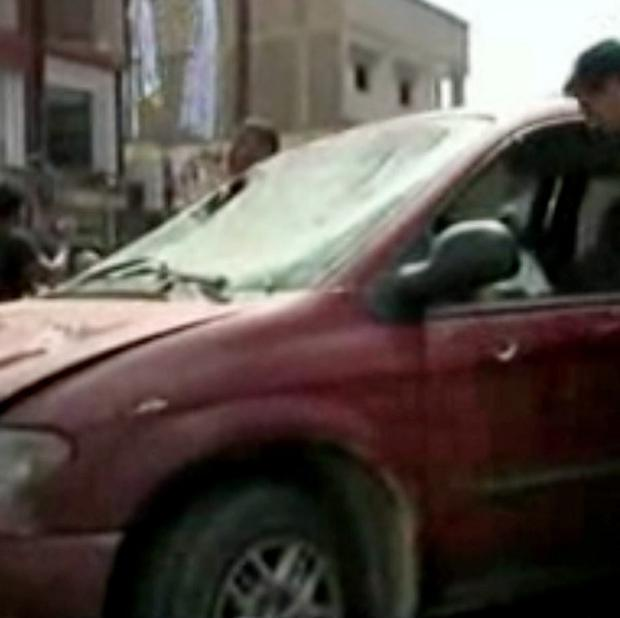 Libyan men inspect the damages of a vehicle at the scene of a car bomb, one of a series of explosions in Benghazi (AP/APTN)