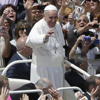 Pope Francis salutes the faithful in St. Peter Square at the Vatican