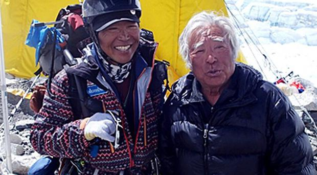 Eighty-year-old Japanese adventurer Yuichiro Miura, right, is greeted by his friend climber Kenji Kondo (AP/Miura Dolphins)