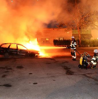 Firemen extinguish a burning car in the Stockholm suburb of Kista (AP)