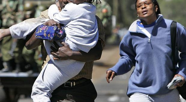 A young girl cries as she is carried by a man and woman fleeing an area set on fire during post-election violence in Kenya (AP/Ben Curtis)