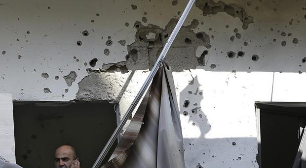 A Lebanese policeman stands at a damaged balcony where a rocket struck an apartment in a building, at Chiyah district south of Beirut (AP)