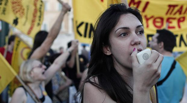 A protester shouts anti-austerity slogans outside the Greek parliament building in central Athens, during a peaceful demonstration (AP)