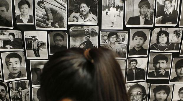 A Hong Kong woman reads a book in front of portraits of victims of the crackdown in Beijing's Tiananmen Square (AP)
