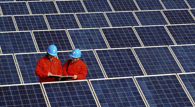 Workers check solar panels at a solar power station on a factory roof in Changxing, eastern China's Zhejiang province (AP)
