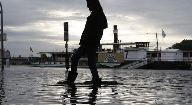 A woman with rubber boots walks across a flooded street under a bridge in Dresden, Germany (AP)