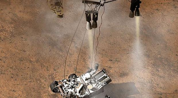 An artist's impression of the rover Curiosity being lowered onto the surface of Mars