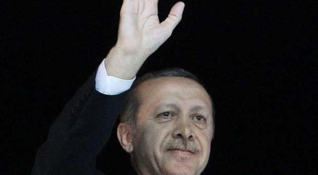 Turkish Prime Minister Recep Tayyip Erdogan waves to the crowd on his arrival at the Ataturk Airport of Istanbul (AP/Thanassis Stavrakis)