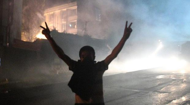 A youth makes the V-sign as a police water cannon shoots during clashes in the Sultangazi suburb, northwestern Istanbul (AP/Thanassis Stavrakis)
