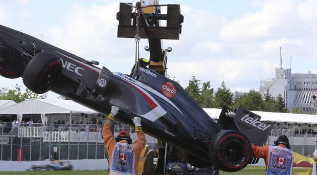 A Sauber car is removed by marshals from the track after crashing during the Formula One Canadian Grand Prix (AP/Tom Boland)