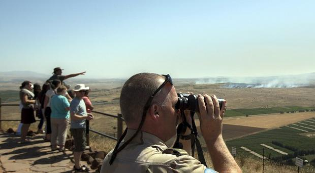 A UN soldier looks through binoculars towards Syria from an observation point in the Golan Heights (AP)