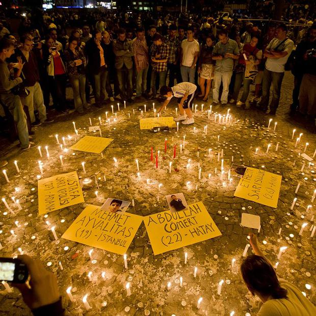 People light candles for the victims of the protests at Taksim square, in Istanbul (AP)