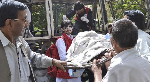 Pakistani volunteers carry the lifeless body of a victim of a bomb blast from the wreckage of a bus in Quetta (AP)