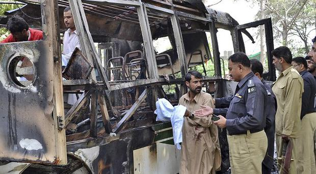 Pakistani police officers and volunteers gather at the wreckage of a bus destroyed in a bomb blast in Quetta (AP)