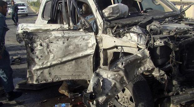 Afghan policemen investigate a damaged car following a suicide car bomb attack in Helmand province (AP)