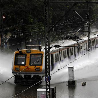 A train moves through a flooded track after heavy rains in Mumbai (AP)
