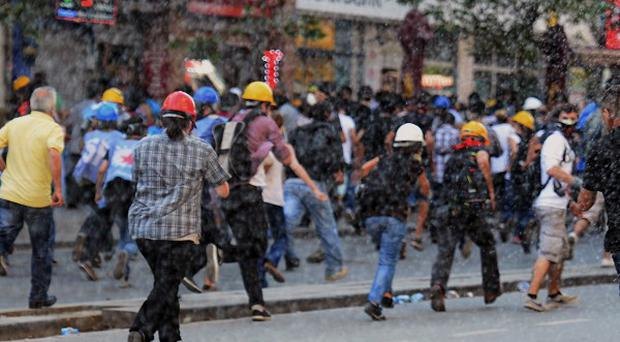 Riot police use water cannons to chase people in Istanbul, Turkey (AP Photo)