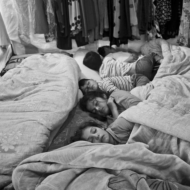Syrian children sleeping inside their family's tent in the Bekaa Valley, Lebanon