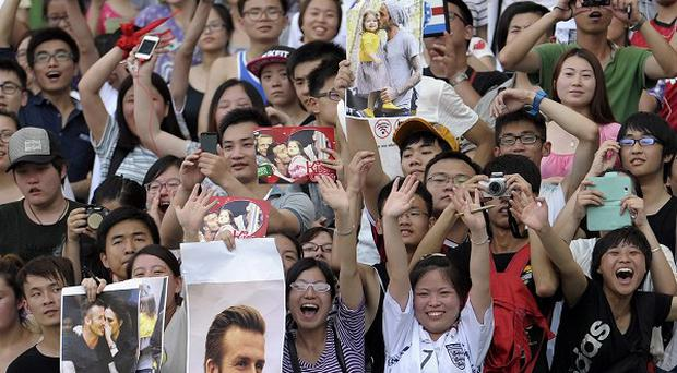 Chinese fans cheer David Beckham cheer during an earlier appearance at a stadium in Nanjing (AP)