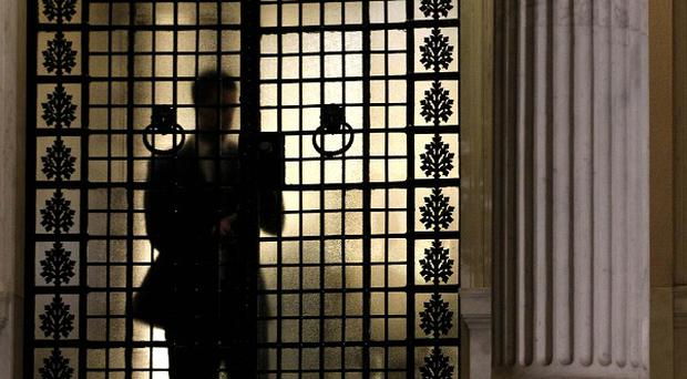 A prime minister's office staff member closes the entrance during a cabinet meeting in Athens (AP/Petros Giannakouris)