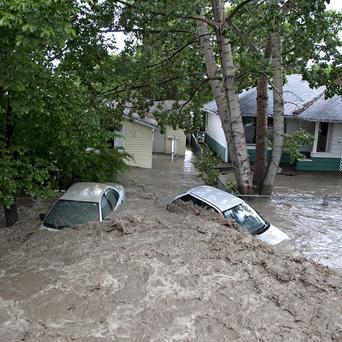Cars are submerged by the flood waters in High River, Alberta (AP/The Canadian Press, Jordan Verlage)