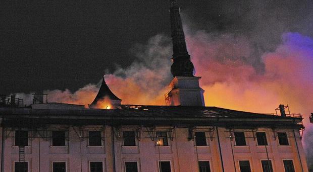 Smoke can be seen above the roof of Riga Castle in Latvia following a fire (AP/Xinhua, Guo Qun)