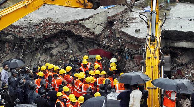 Indian rescue workers look for trapped people after a residential building collapsed in Mumbai (AP)
