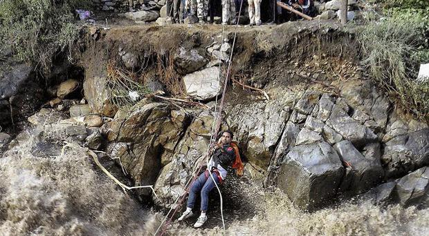 Indo-Tibetan Border Police (ITBP) use a rope to rescue stranded pilgrims cross a river swollen by flood waters (AP)
