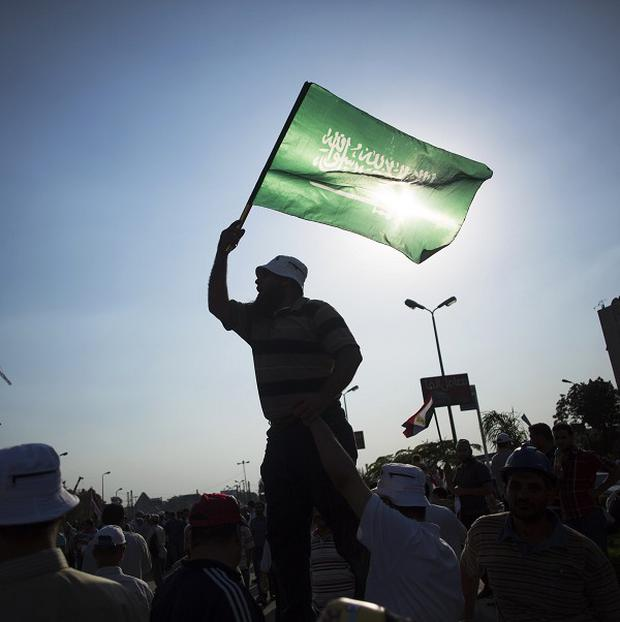 An man waves an Islamic flag during a rally supporting President Mohammed Morsi in Cairo, Egypt (AP/Manu Brabo)