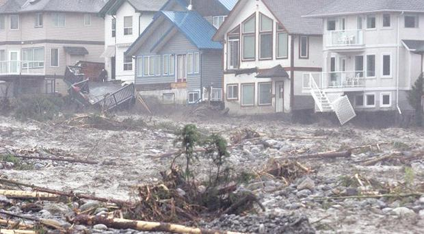 Homes along Cougar Creek in Canmore, Alberta, which is struggling to deal with floods (AP/The Canadian Press, Rocky Mountain Outlook, Craig Douce)