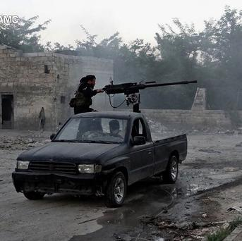 A Syrian rebel fires a heavy machine gun towards Syrian soldiers loyal to President Bashar Assad in Aleppo, Syria (AP/Aleppo Media Center AMC)
