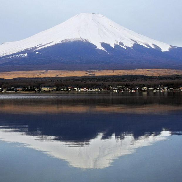Mount Fuji's peak in nearly symmetrical, snowcapped cone is reflected on the surface of Lake Yamanaka (AP)