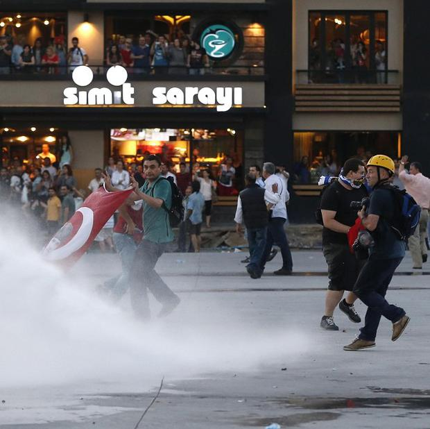 Protesters are sprayed with water canon during clashes with riot police in Istanbul, Turkey (AP/Petr David Josek)