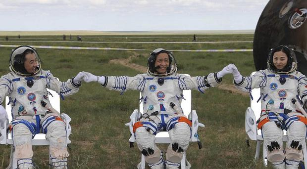 Astronauts Zhang Xiaoguang, Nie Haisheng and Wang Yaping join hands after exiting the re-entry capsule of China's Shenzhou 10 spacecraft (AP)