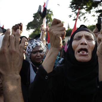 Egyptian protesters chant against the Muslim Brotherhood and Egyptian President Mohammed Morsi outside the Ministry of Defence in Cairo (AP)