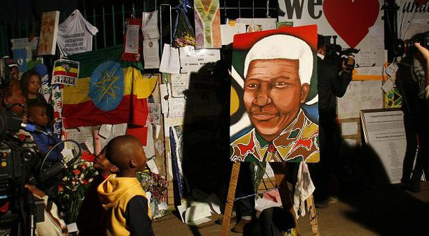 People stand outside the Mediclinic Heart Hospital where former South African president Nelson Mandela is being treated in Pretoria (AP)
