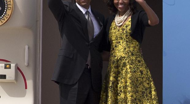 US President Barack Obama and First Lady Michelle Obama wave as they board Air Force One to depart for South Africa (AP)